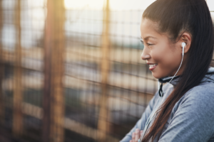Music for the gym is something that can motivate you, relax you, help you focus and give you the strength you need to accomplish your goals! Woman outside listening to music on headphones.