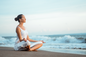 Woman in white on beach meditating