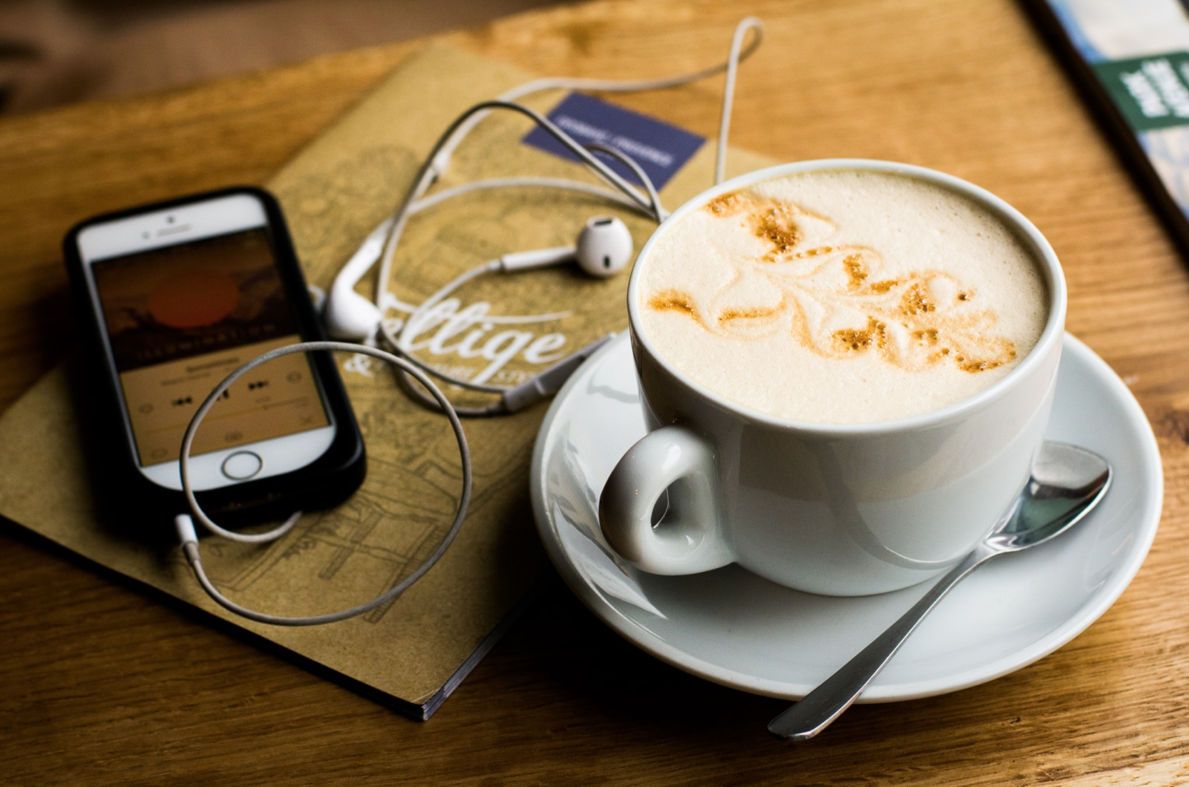 Playlists To Reduce Anxiety. While listening try mindfulness meditation, some yoga online and essential oils for anxiety with a diffuser. Gourmet coffee with iPhone and headphones at coffee shop.