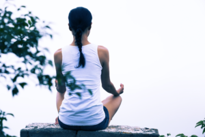 Woman in white shirt sitting and meditating